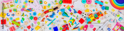 Fotomural Variety of plastic and wooden kids toys on light wooden background