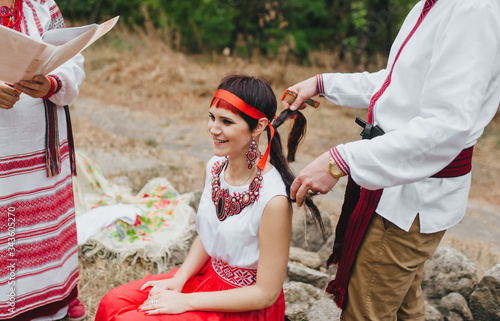 The groom braids the braid of the sitting bride in Ukrainian attire and jewelry in the style of pagan traditions Wallpaper Mural