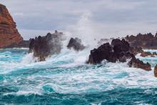 Ocean Waves Break Against Coastal Cliffs On A Cloudy Summer Day