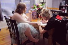 Woman Applying Nail Polish On Teenage Girl Hand At Home