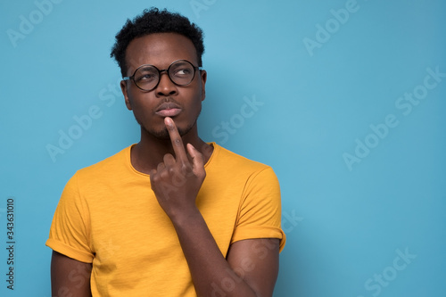 Young african american man, student with finger in mouth in deep thought Fototapet