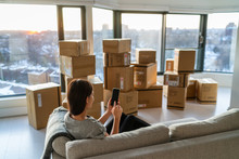 Home Move Out Of Apartment Moving Boxes Woman Using Online Movers Services On Mobile Phone App Easy Pick-up With Packages For New Home. Asian New Homeowner Girl Happy Sitting In Sofa.