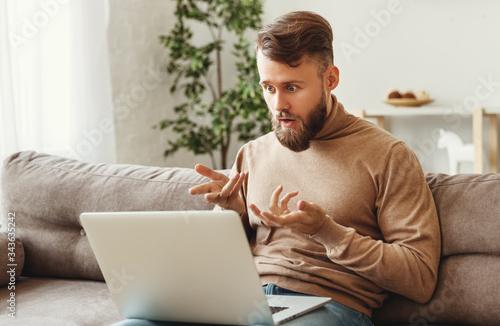 Shocked man using laptop at home. Wallpaper Mural
