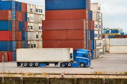 Fotografía Cargo containers stack, semi truck in an intermodal shipping hub, container term