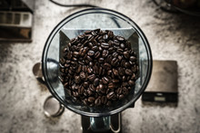 Directly Above Shot Of Roasted Coffee Beans In Mill On Table
