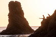 Silhoutte of a man doing handbalance at the edge of a clif at the beach and his dog