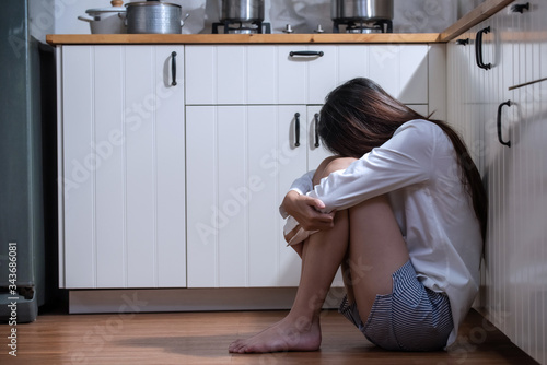 Cuadros en Lienzo Depressed young beautiful Asian woman sitting on kitchen floor with hugging knees