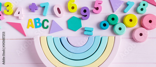 Obraz na plátne Wooden toy rainbow, numbers, blocks, pastel color arc on pink background
