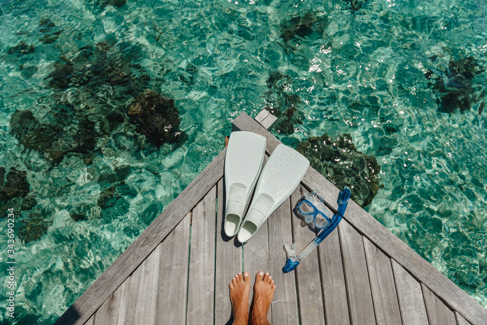 Fototapeta Beach vacation snorkel girl snorkeling with mask and fins. Equipment for snorkeling. Woman legs on wooden pier with snorkeling equipment