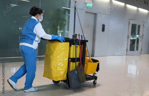 Obraz na plátne Closeup of janitorial, cleaning equipment and tools for floor cleaning and woman woker