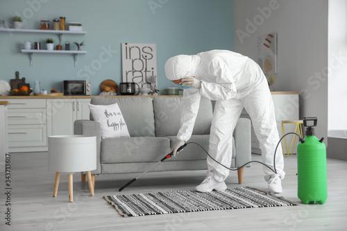 Worker in biohazard suit disinfecting house