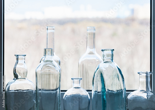 Fototapeta many empty drunk bottles and view of city park through home window on sunny spring day on background obraz