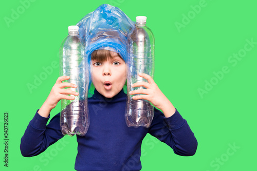 Photo Girl hold trash bag and plastic bottle and shows interest in environmental issues isolated on green background