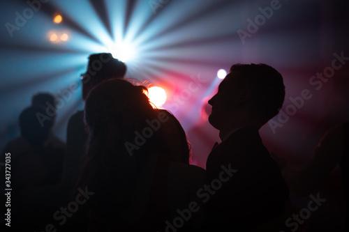 Valokuva Ciemne sylwetki tańczących ludzi na tle biało czerwonych świateł