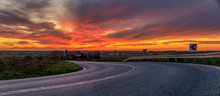Winding Asphalt Road Against The Backdrop Of A Dramatic, Fiery Sunset