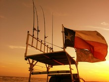 Low Angle View Of Texas State Flag With Fishing Rods On Platform Against Sunset Sky