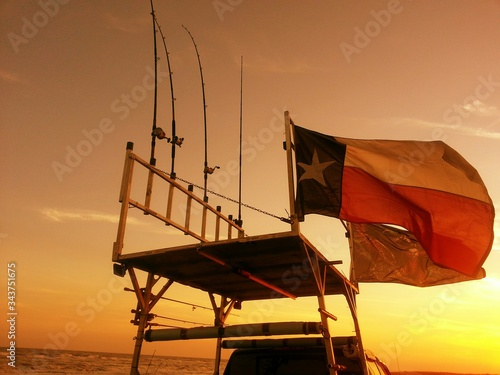 Obraz na plátně Low Angle View Of Texas State Flag With Fishing Rods On Platform Against Sunset