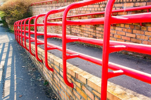Shot of inclined  outdoor wheelchair ramp with red metal handles Canvas