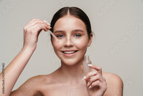 Photo Image of cheerful shirtless woman applying face serum and smiling