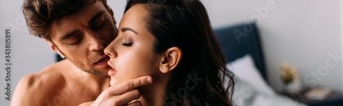 Fototapeta Man with closed eyes kissing passionate girl in bedroom, panoramic shot