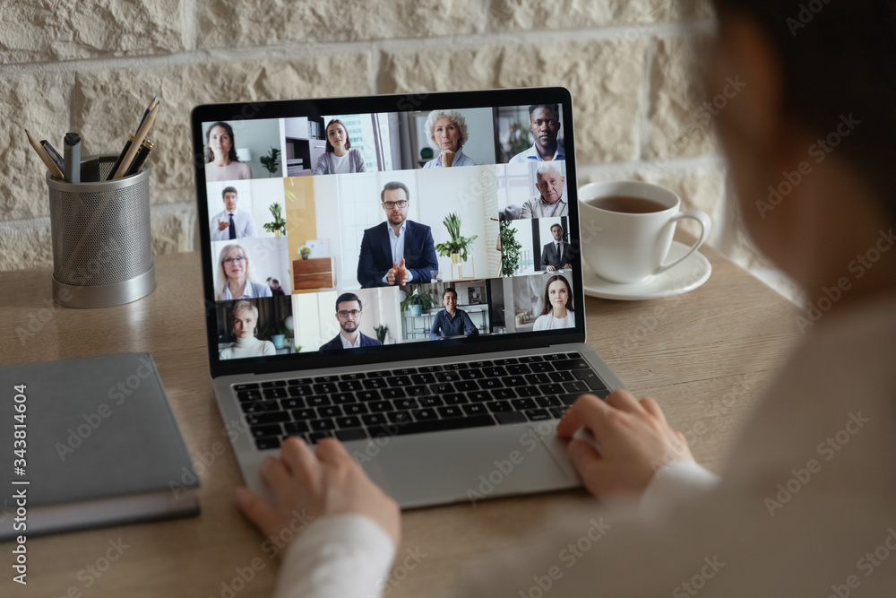 Fototapeta Rear close up view of diverse businesspeople talk on webcam conference conversation brainstorming online, employees colleagues speak on video call on laptop, engaged in internet meeting or briefing