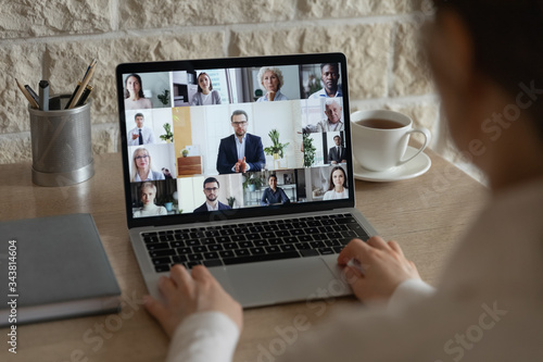 Fototapeta Rear close up view of diverse businesspeople talk on webcam conference conversation brainstorming online, employees colleagues speak on video call on laptop, engaged in internet meeting or briefing obraz