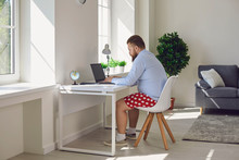 Online Work At Home. Funny Fat Businessman In Red Shorts Works Communicates Using Laptop At Home.