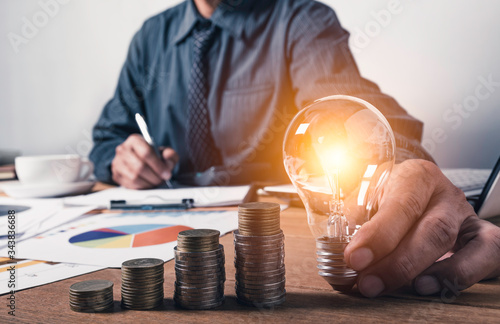 Fototapeta Business man holding a light bulb with coins money and copy space for accounting, ideas and creative concept. obraz