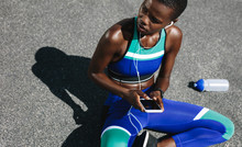 Fit Woman On Road Taking A Break After Outdoor Workout