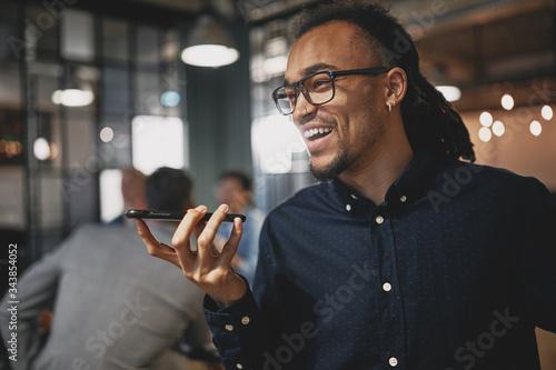 Fotografie, Tablou Laughing businessman talking on speakerphone in an office