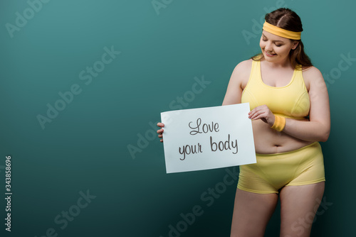 Plus size sportswoman smiling and looking at placard with love your body letteri Wallpaper Mural