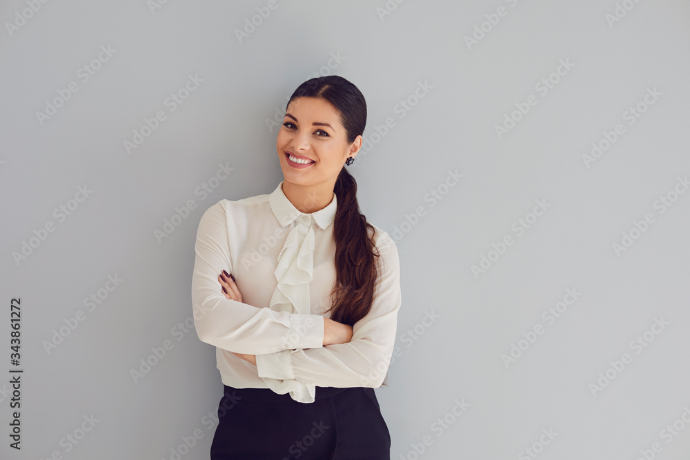 Fototapeta Young woman in white shirt smiling laughs joyful happy positive on a gray background.