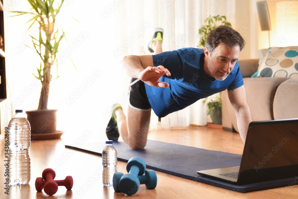 Fototapeta Man doing sports looking at a laptop at home