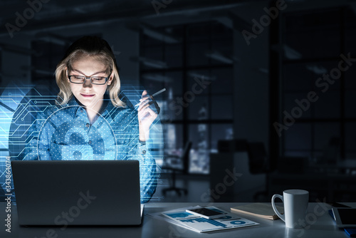 Beautiful blonde in dark office working on laptop and getting net access Wallpaper Mural