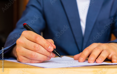 Photographie Close-up of the hands of a well-dressed man in a blue suit and white shirt signing a document on a desk