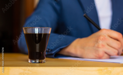 Close-up of a glass of coffee on the table of a well-dressed man in a blue suit and a white shirt writing or signing a blueprint at home or office Poster Mural XXL
