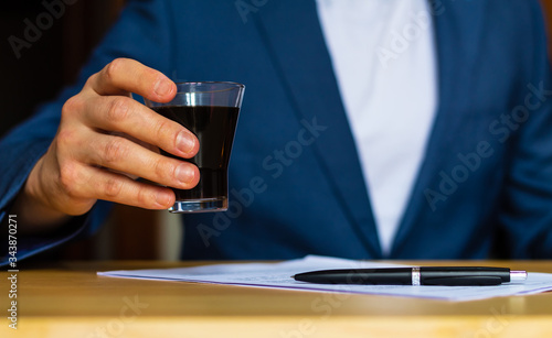 Close-up of the hands of a well-dressed man in a blue suit and a white shirt drinking a glass of coffee on a desk Tableau sur Toile