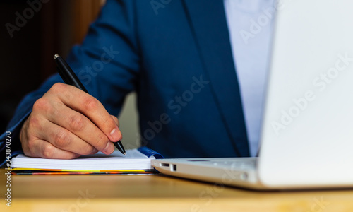Close-up of the hands of a well-dressed man in a blue suit and a white shirt writing in an agenda or a notebook, with a laptop on a desk Tableau sur Toile