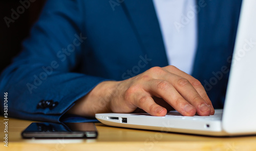 Photographie Close-up of the hands of a well-dressed man in a blue suit and a white shirt using a laptop at a desk