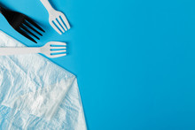 White And Black Plastic Forks And Transparent Plastic Bag On A Blue Background. The Global Problem Of Environmental Pollution. Copy Space. Flat Lay Minimalism
