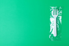 White Plastic Fork On A Green Background. The Global Problem Of Environmental Pollution. Copy Space, Flat Lay Minimalism