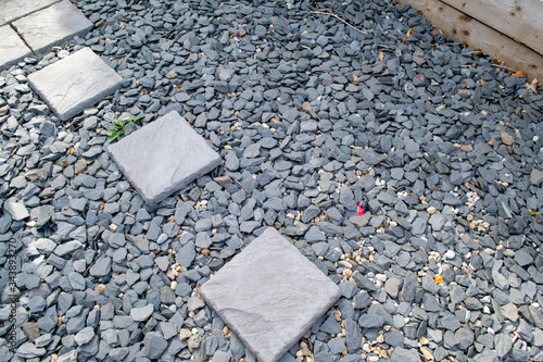 Photo Grey aggregate and small textured rocks/stones with square textured block paving slabs irregularly laid out