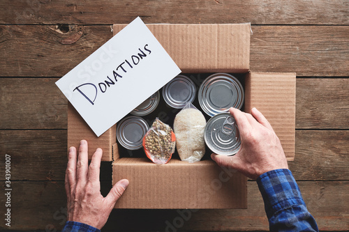 Fototapeta a person packing a donation box with food items obraz