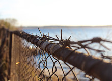 Old Rusty Barbed Wire On A Chain-link Fence.