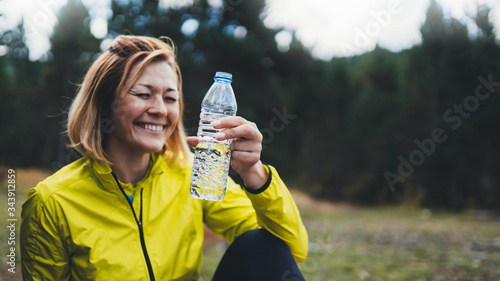Happy sport girl laughing quenches thirst after fitness Canvas Print