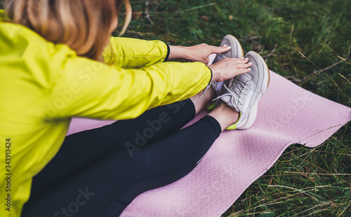 Foto Girl exercising outdoors in sun summer day, fitness woman in trainer stretching exercises legs training outside on green park