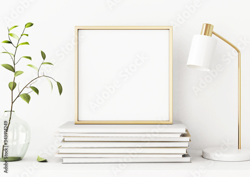 Photo Interior poster mockup with square gold metal frame on pile of books, green tree branch in vase and desk lamp on empty white wall background