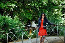 Beautiful Woman Standing On Overpass Against Trees In Park