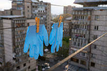 Disposable Medical Gloves Hanging On Pegged Clothesline For Reused. Washed Surgical Gloves. Used Surgical Gloves Were Washed And Being Dried.