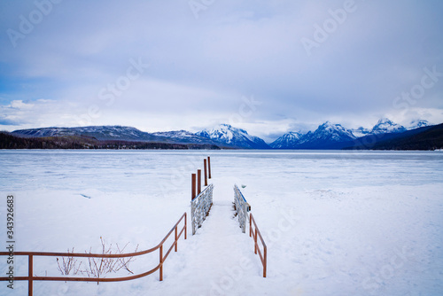 Vászonkép Icy path to ice covered lake with mountains in the background in Glacier Nationa